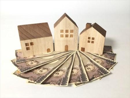 お札の上にのった家の模型