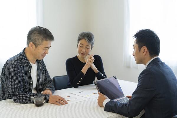 不動産売買・査定について話し合う夫婦と男性